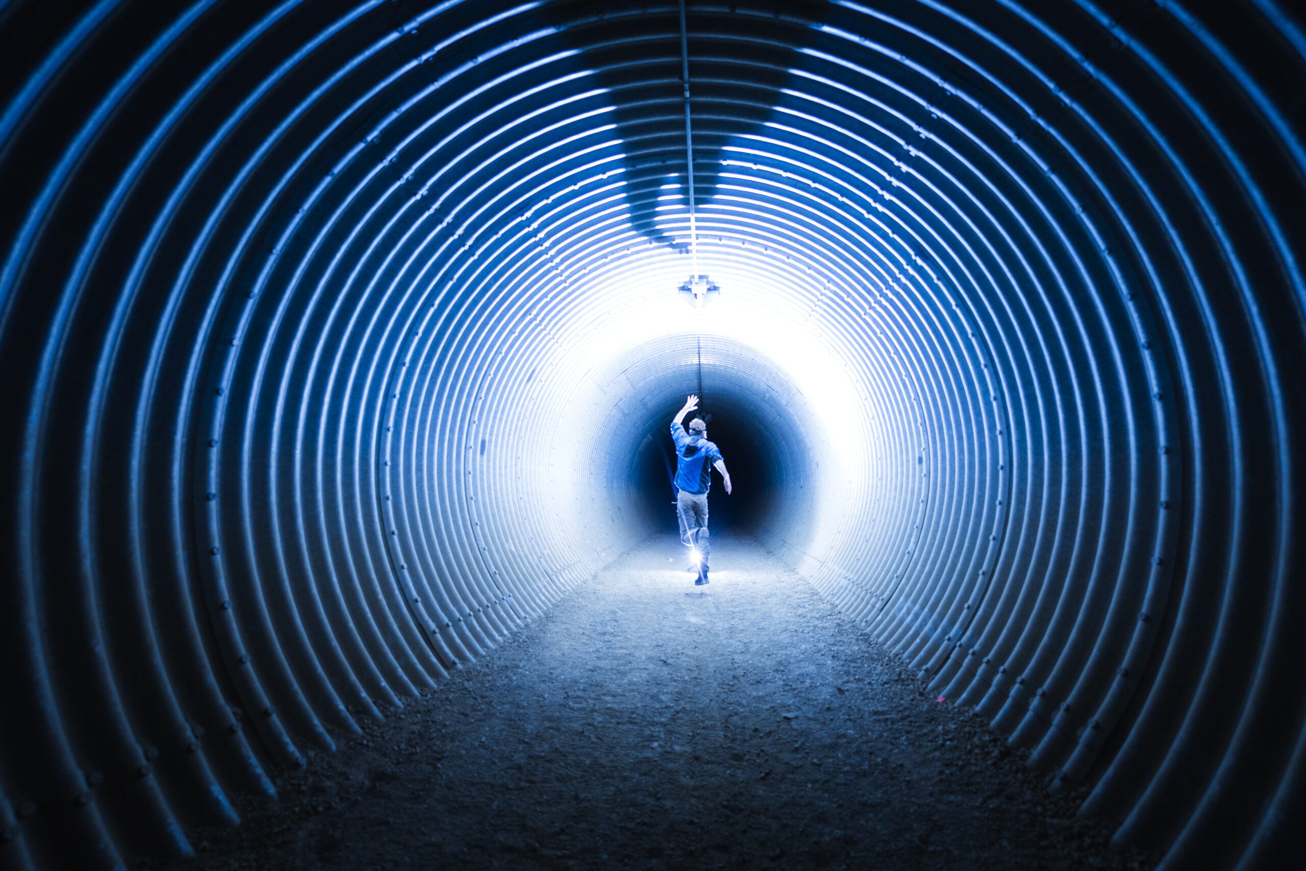 A person running inside a highway underpass at night in Winfield, Lake Country, British Columbia, Canada